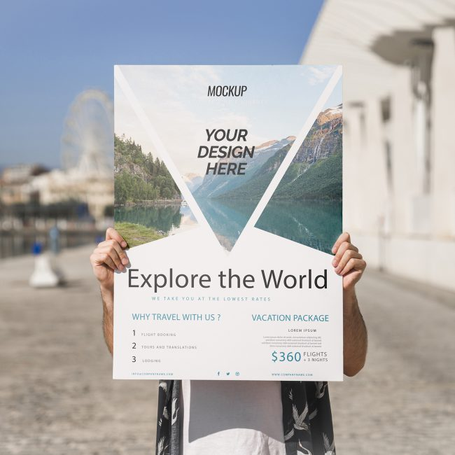 "A man holds a large outdoor poster with the words ""explore the world"" on it and a trio of photos of nature."