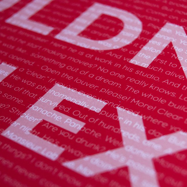 Satin poster close up. Red background with large white text and small white text overlay.