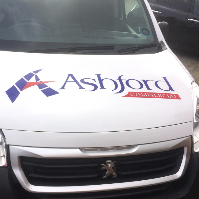 The front of a van has vinyl decals to display the Ashford Commercial logo.