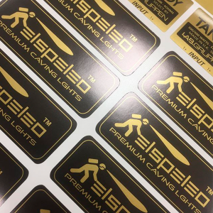 "A page of black and gold ""Elspeleo Premium Caving Lights"" stickers with gloss surface."