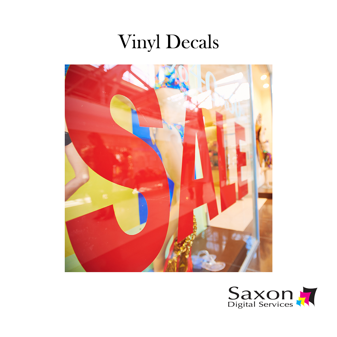 "Vinyl Decals by Saxon Digital Services. Large red letters read ""SALE"" outside a clothing shop."