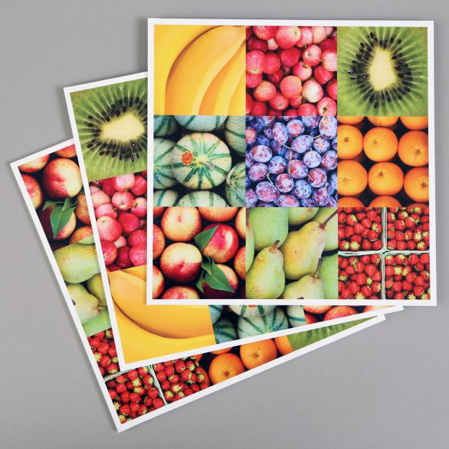 A pile of foamex boards that feature photographs of fruit (e.g. bananas, strawberries and apples)