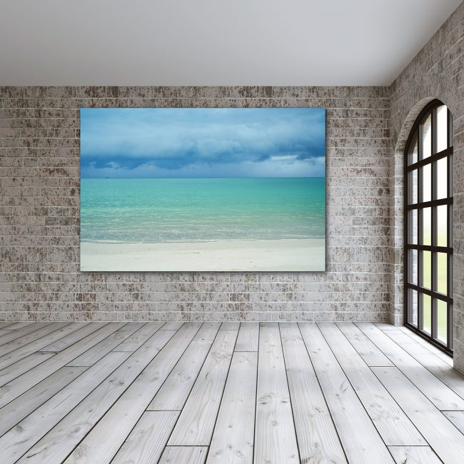 A dibond board in a large room with brick walls and wooden flooring. It is an image of the ocean with blue skies and white sand.