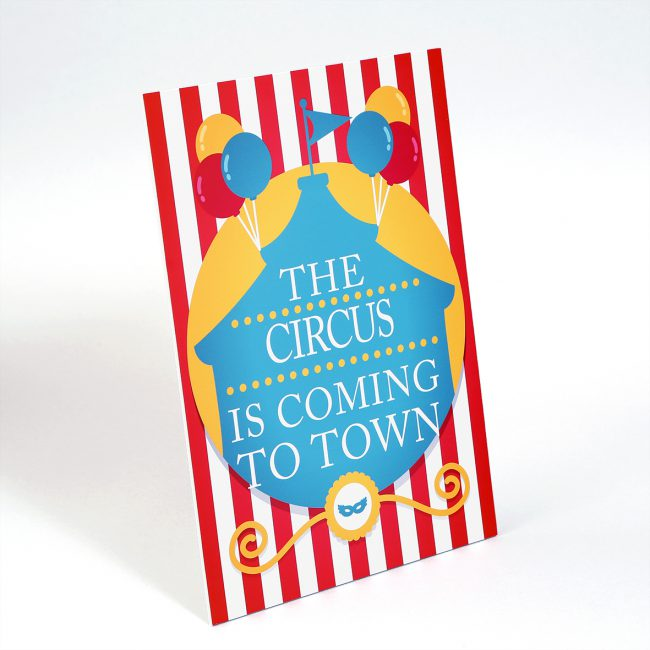 "A strut card with a red and white striped background. It reads ""the circus is coming to town!"""