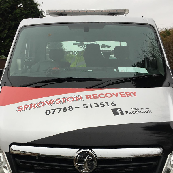 The front of a van with vinyl decals. It displays the Sprowston Recovery logo, phone number and Facebook details.