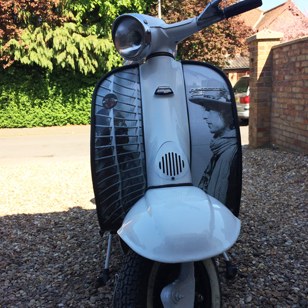 A white moped with a vinyl graphic across its front. It is an image of John Lennon looking into some slated blinds to look at Yoko Ono.