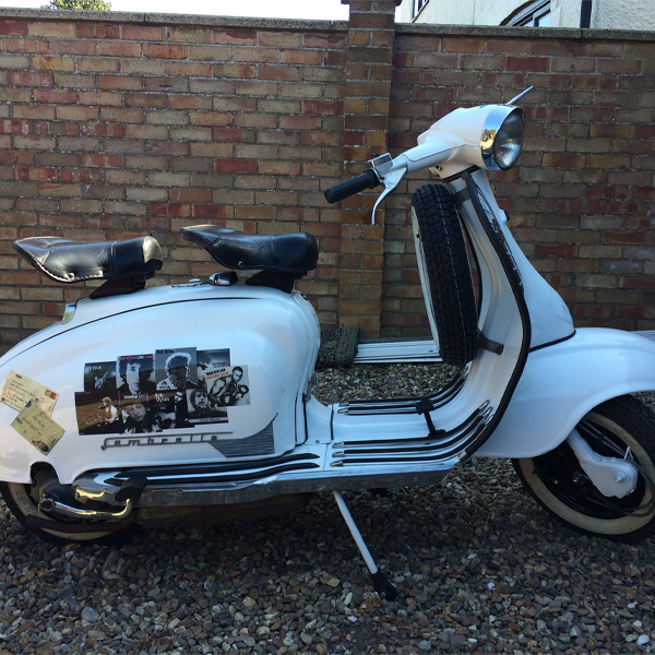 A white moped with a vinyl graphic across its side. It is a collection fo vintage mod musicians, including Bob Dylan.