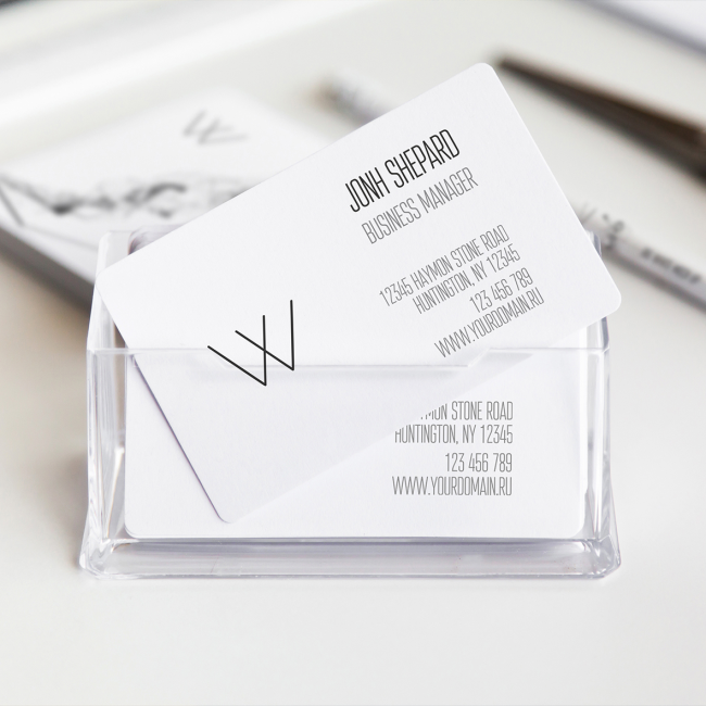 A clear glass box holds a pack of business cards. The design is minimalist with curved edges and narrow writing.