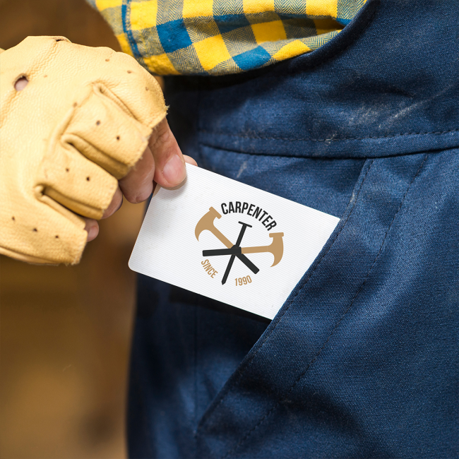 A carpenter pulls a business card out of his pocket. He is wearing mustard fingerless gloves and a blue and yellow checked shirt.