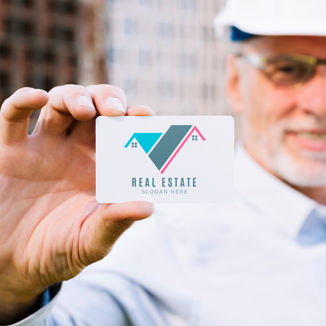 A construction man holds out a business card for a real estate company. It has rounded edges and abstract logo.