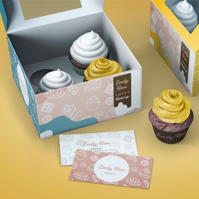 A personalised box of chocolate cupcakes with white and yellow frosting. A pile of white and pink business cards with bakery imagery on it.