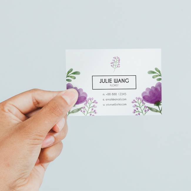 A hand holds a business card for Julie Wang, Florist. It has a watercolour floral design with a round typeface.