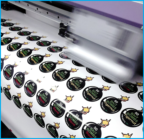A large printing machine prints rows of cartoon-style bomb stickers that read: